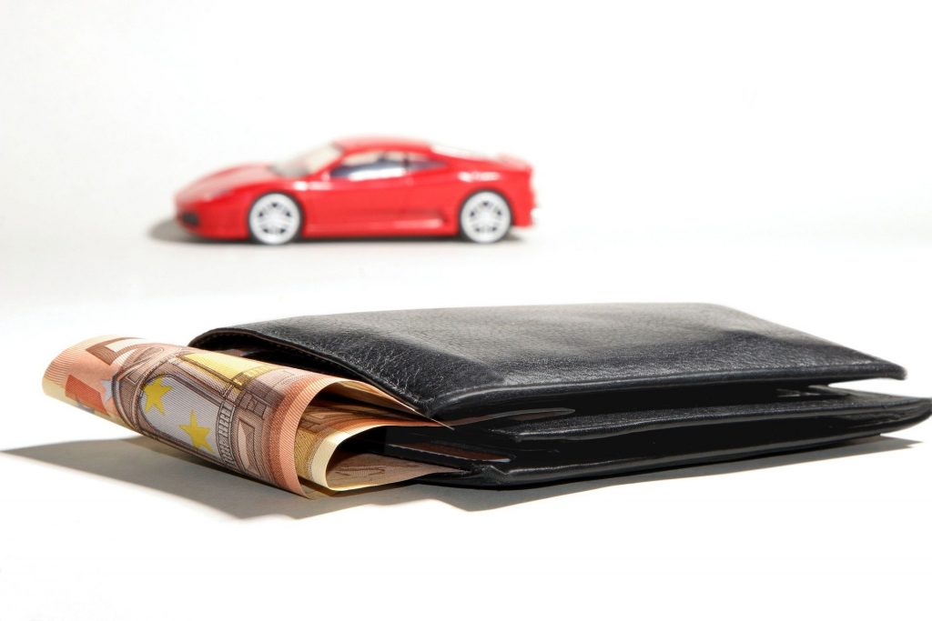 A wallet in the foreground and a red car in the background.